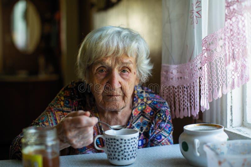 Une femme triste pluse âgé buvant tristement du thé photos libres de droits