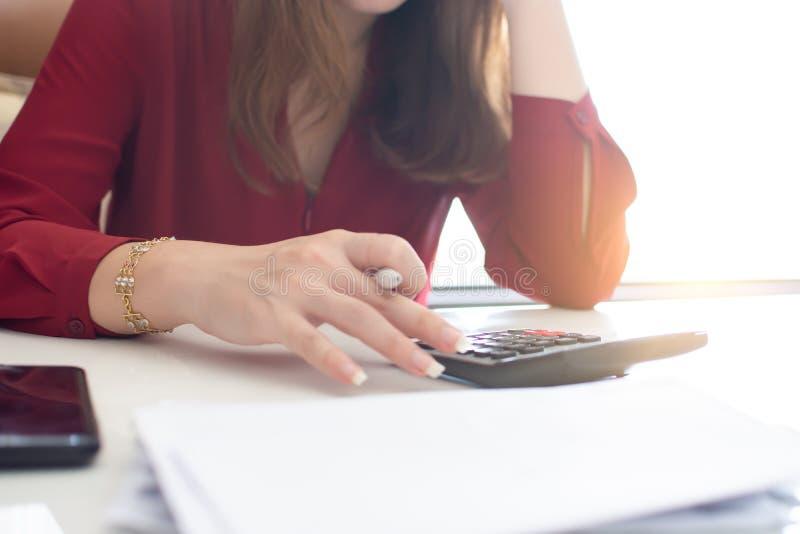 Une femme utilise la calculatrice pour le travail photo libre de droits