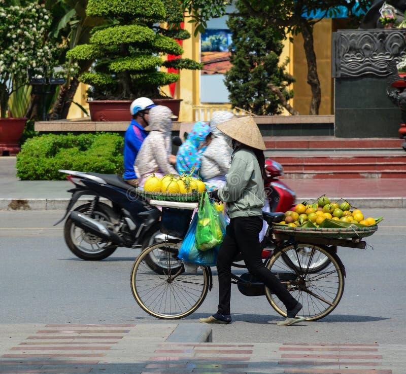 Une femme vendant les fruits locaux devant le monument photographie stock