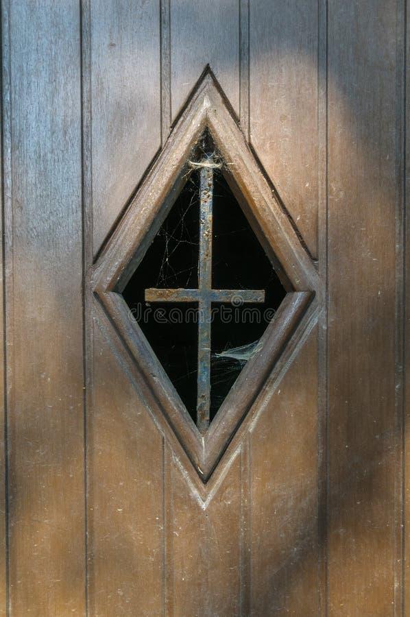 Une fenêtre avec des toiles d'araignée et une croix de fer dans une porte en bois photos stock