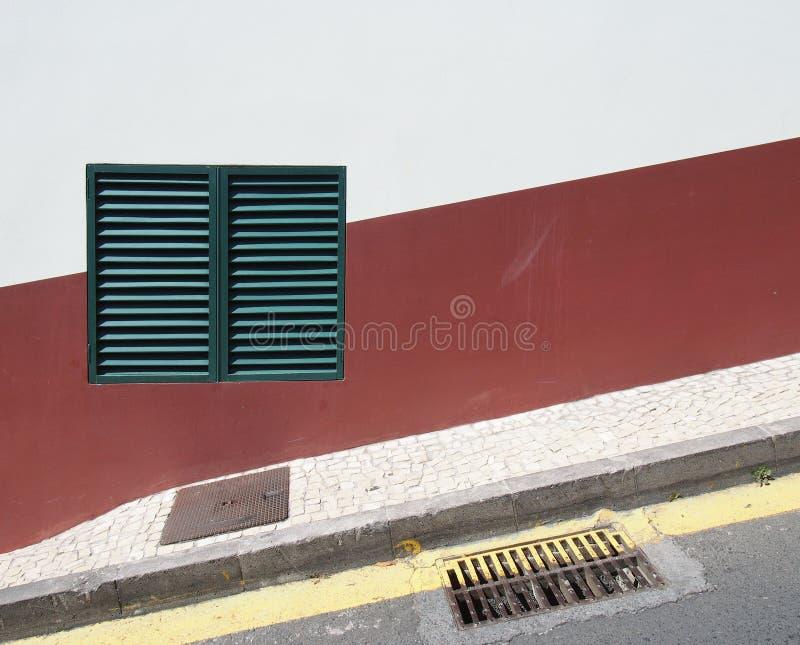 une fenêtre fermée à volets verte sur un mur rouge et blanc de maison sur une rue en pente avec la ligne se garante jaune et le t image libre de droits