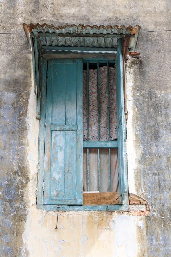 Une fenêtre ouverte avec des grils et un toit de tôle images stock