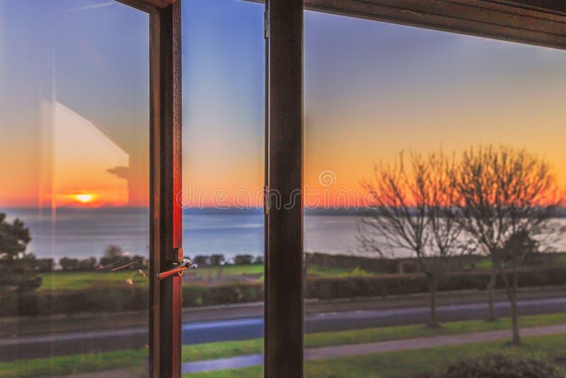 Une fenêtre ouverte, avec une serrure principale et un cadre coloré en bois attrape la réflexion d'un coucher du soleil photos stock