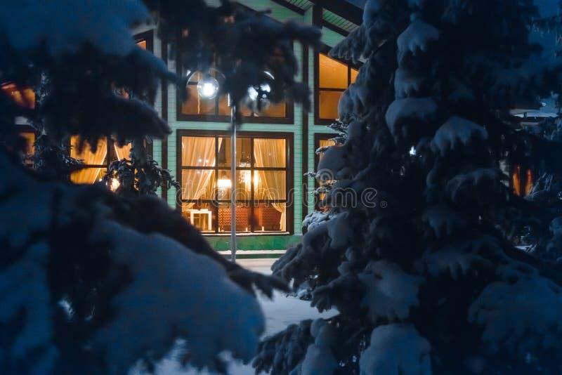 Une fenêtre reculée profondément dans le cottage de forêt d'hiver parmi les pins image stock