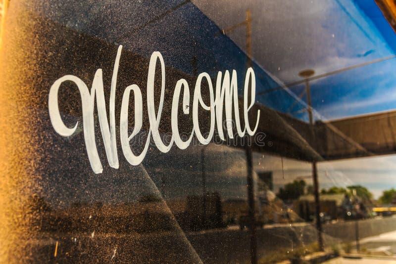 Une fenêtre sale et sale avec l'accueil écrit là-dessus photos stock