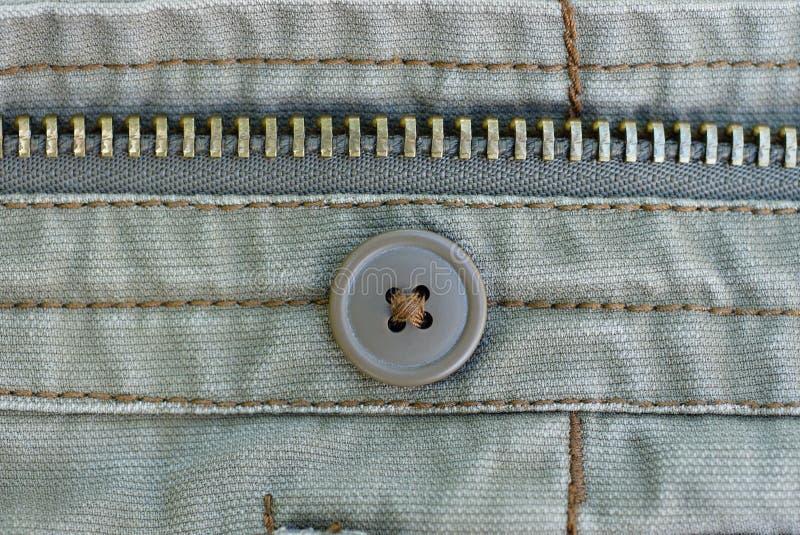 Une fermeture éclair brune de bouton et en métal sur le coton gris image stock