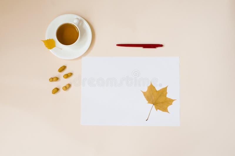 Une feuille blanche de papier, un stylo rouge, des feuilles d'automne et une coupe de thé chaud sur fond beige photos stock