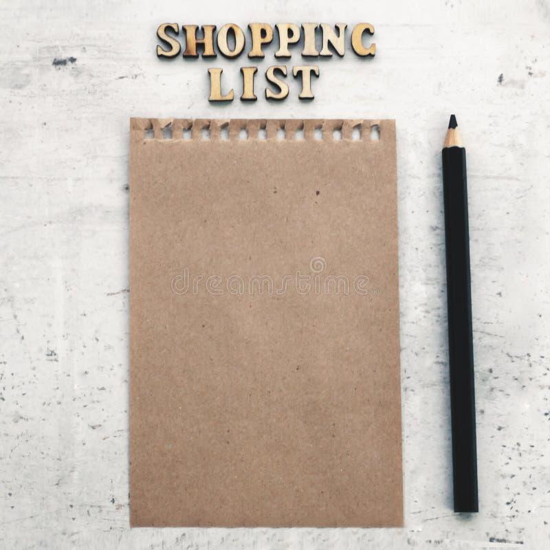 Une feuille de papier de métier à côté de elle est une liste d'achat et un crayon noir Foyer sélectif image stock