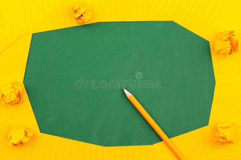 Une feuille orange de mensonges de papier sur un conseil pédagogique vert constituant un cadre pour le texte pr?s du crayon et de photos libres de droits
