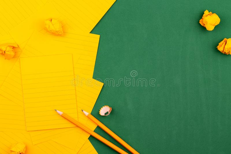 Une feuille orange de mensonges de papier sur un conseil p?dagogique vert constituant un cadre pour le texte pr?s du crayon et de photo libre de droits