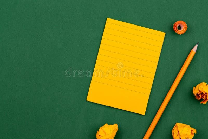 Une feuille orange de mensonges de papier sur un conseil p?dagogique vert constituant un cadre pour le texte pr?s du crayon et de images libres de droits