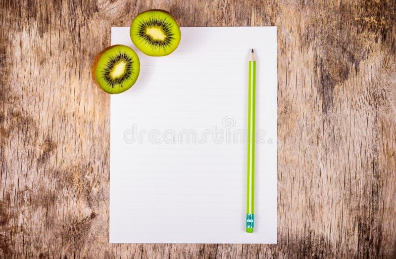 Une feuille vide de livre blanc et de crayon Deux moitiés de kiwi juteux sur le conseil en bois photo libre de droits
