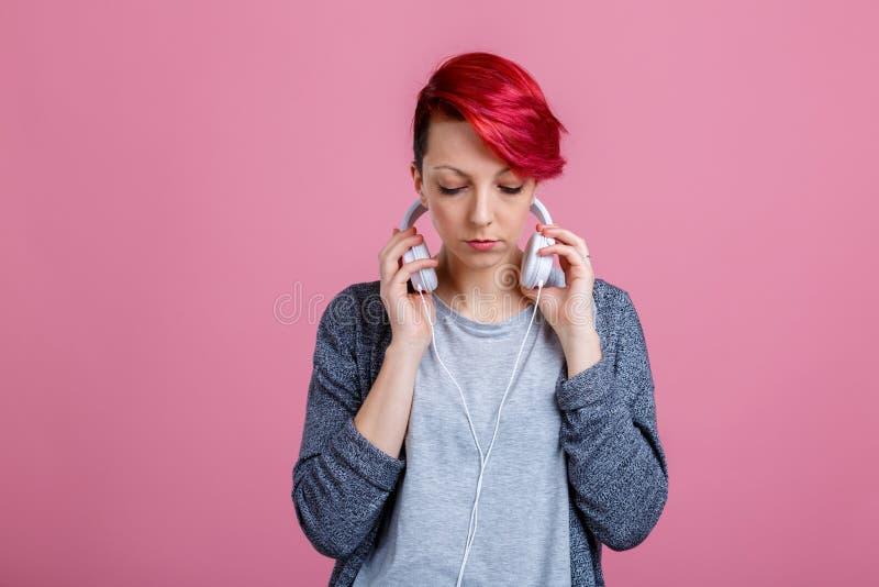 Une fille, écoutant la musique sur des écouteurs et regardant vers le bas photo stock