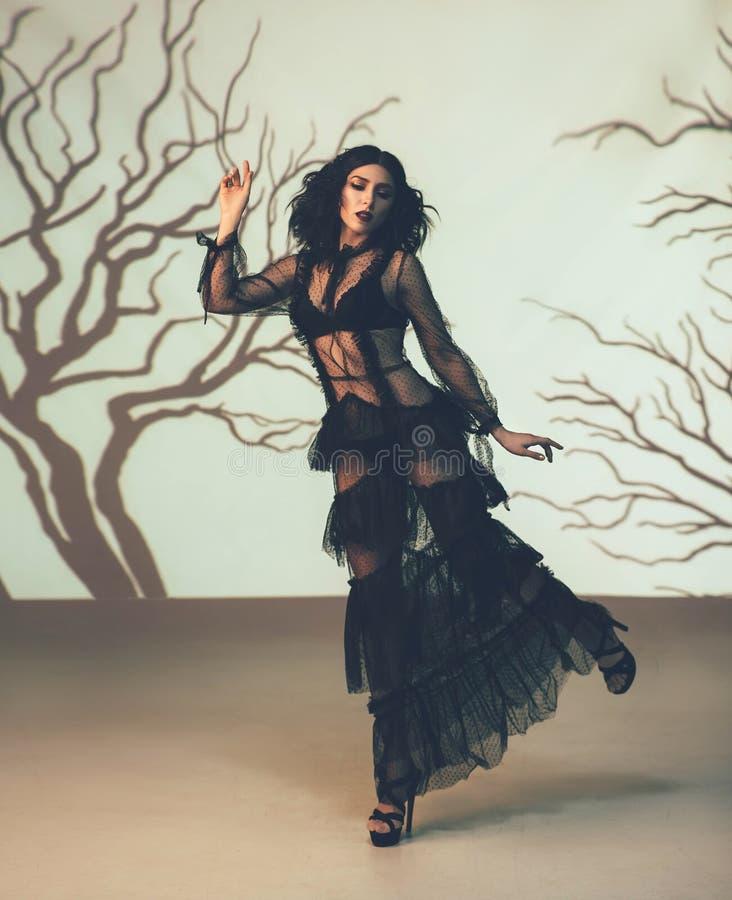 Une fille étrangère dans un noir, transparent, robe de vintage posant contre le contexte d'une forêt sombre, qui est créée par image stock