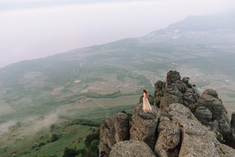 Une fille admirant l'aube ou le coucher du soleil du soleil dans un endroit pittoresque dans les montagnes photos stock