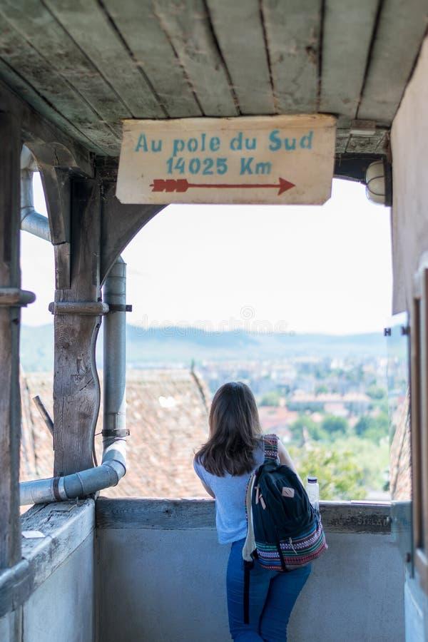 Une fille admirant la vue de la tour d'horloge de Sighisoara un jour ensoleillé images stock