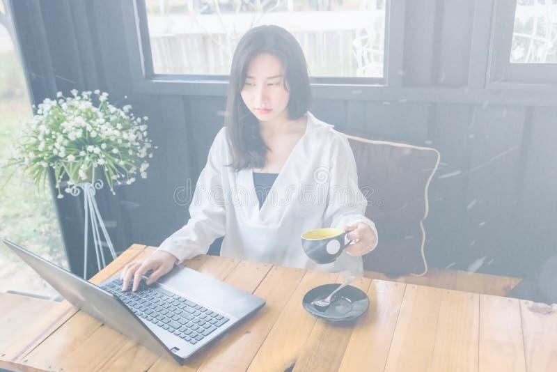 Une fille asiatique dans la chemise blanche joue le carnet sur la table en bois dans la chambre noire image libre de droits