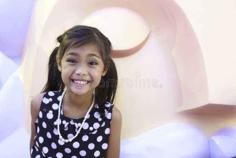 Une fille asiatique mignonne dans la robe noire avec les cheveux blancs de tache et de lien apprécie avec la grande poupée image libre de droits