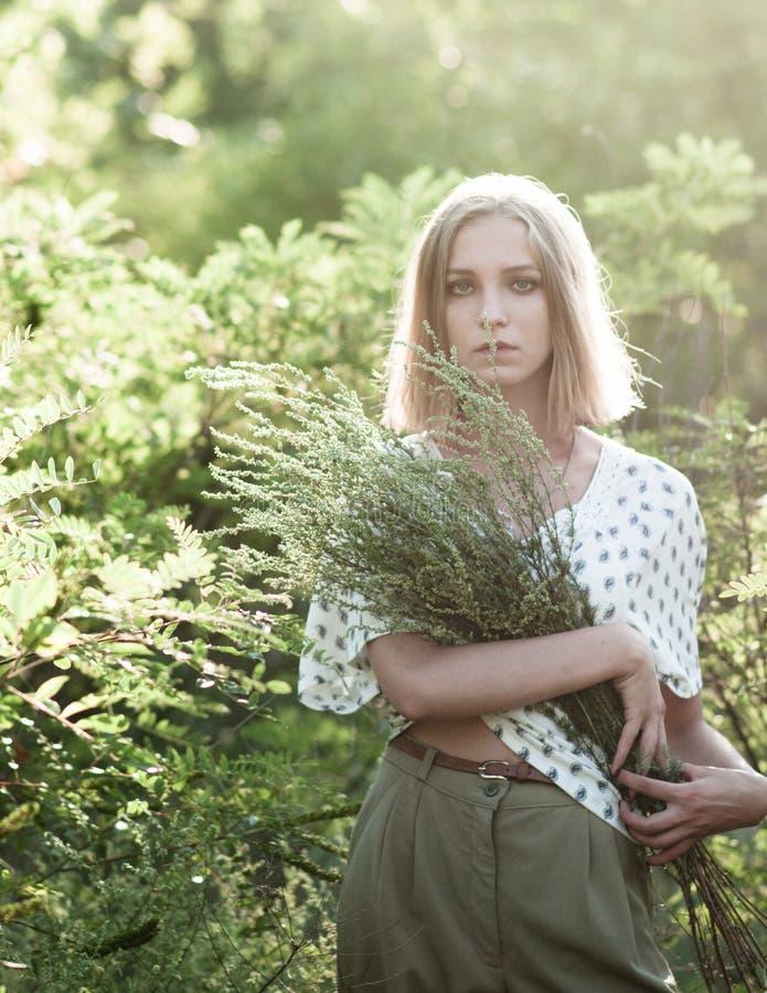 Une fille assez élégante tient un bouquet de haute herbe de mauvaise herbe photographie stock libre de droits