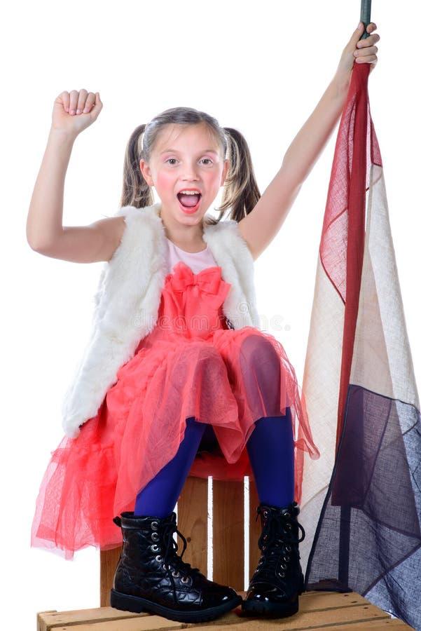 Une fille assez petite s'asseyant sur une boîte avec un drapeau français photo stock