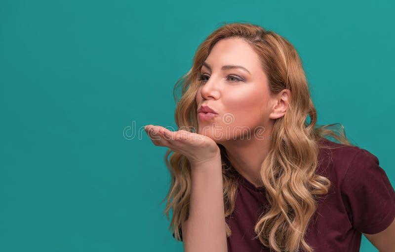 Une fille attirante envoie un baiser ou des coups sur la main Pose blonde sur le fond bleu image stock