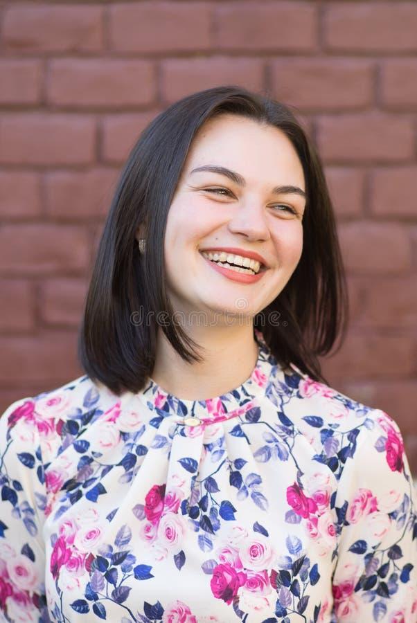 Une fille attirante souriant dans la perspective d'un mur de briques images stock