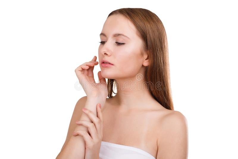 Une fille, aucun maquillage et avec la peau propre de son visage, ne regarde vers le bas et tient ses mains près de son visage D' images stock