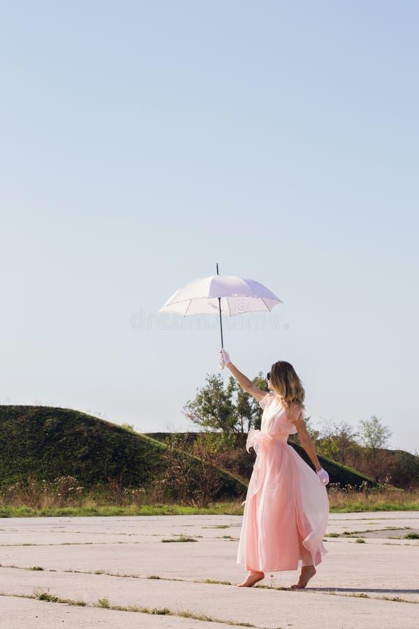 Une fille aux pieds nus dans une robe rose photo libre de droits