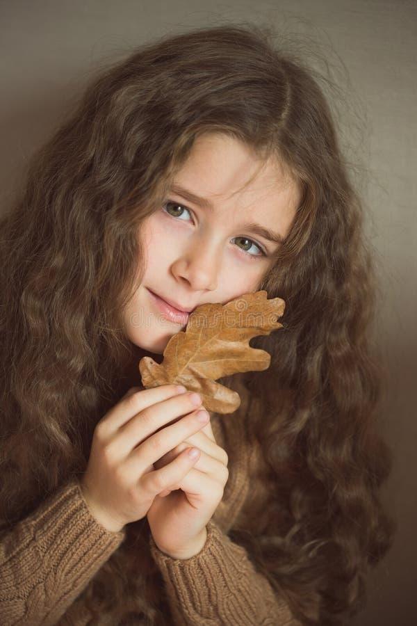 Une fille avec de longs cheveux bouclés presse une feuille de chêne d'automne à son visage couleur de moutarde de chandail tricot images libres de droits