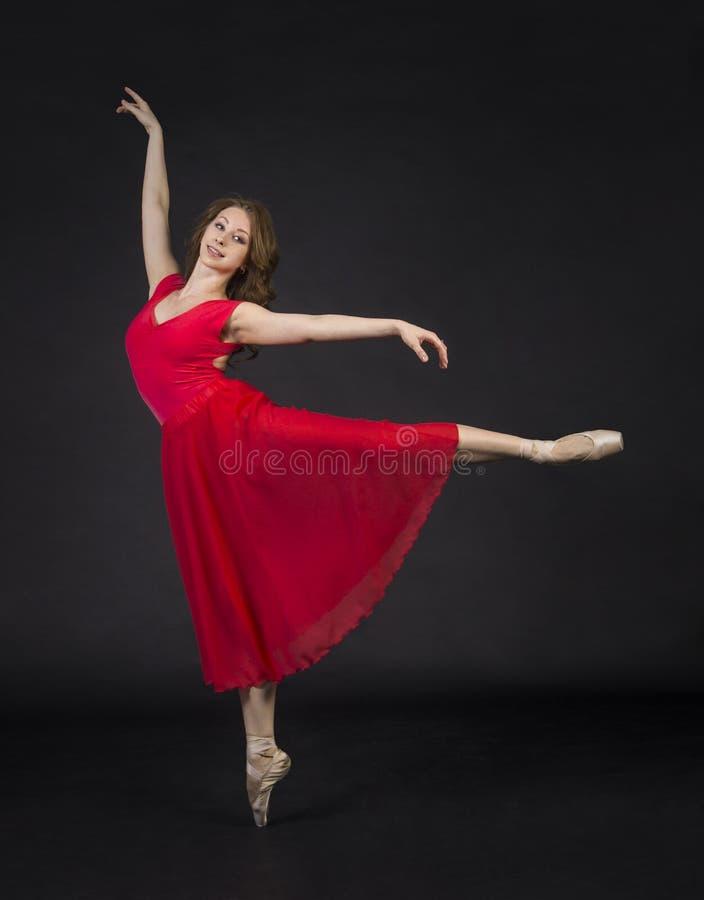 Une fille avec de longs cheveux, dans le ballet rouge et dansant image stock