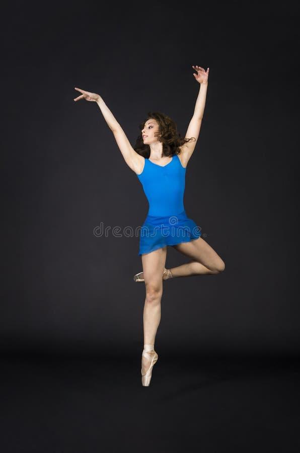 Une fille avec de longs cheveux, dans une robe bleue et des chaussures de Pointe, ballet de danse image libre de droits