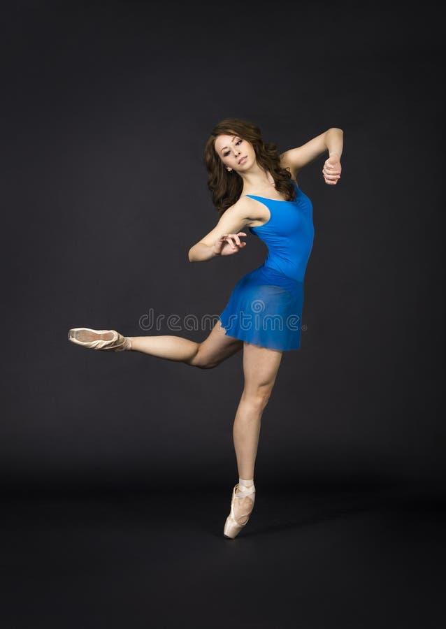 Une fille avec de longs cheveux, dans une robe bleue et des chaussures de Pointe, ballet de danse photos stock