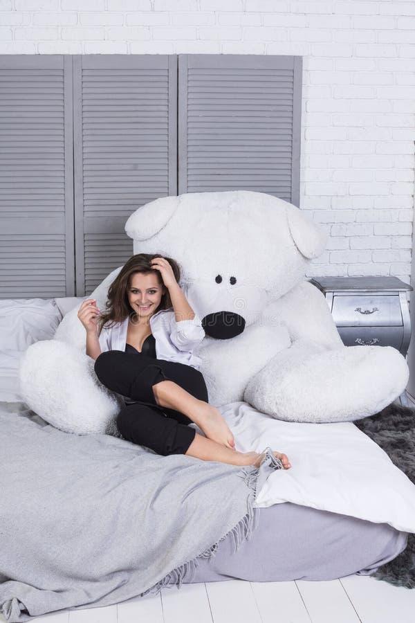 Une fille avec de longs cheveux habillés dans des jeans noirs et une chemise blanche se reposant sur le lit avec la grande étrein images stock