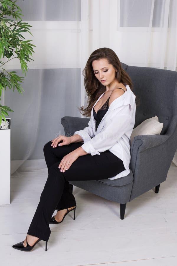 Une fille avec de longs cheveux s'est habillée dans des jeans noirs et une chemise blanche se reposant sur le fauteuil Équipement photos stock