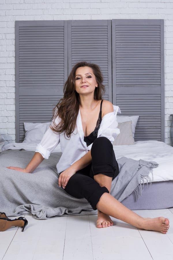 Une fille avec de longs cheveux s'est habillée dans des jeans noirs et une chemise blanche se reposant sur le lit Équipement occa photographie stock