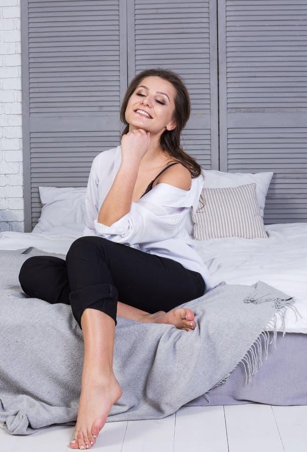 Une fille avec de longs cheveux s'est habillée dans des jeans noirs et une chemise blanche se reposant sur le lit Équipement occa image stock