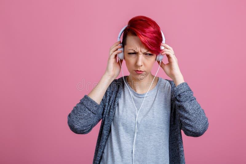 Une fille avec des écouteurs, est des grimaces son visage de mécontentement photos libres de droits
