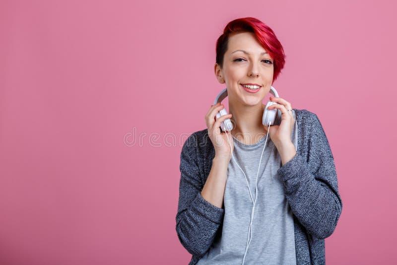 Une fille avec des écouteurs sur son cou est sourire photo libre de droits