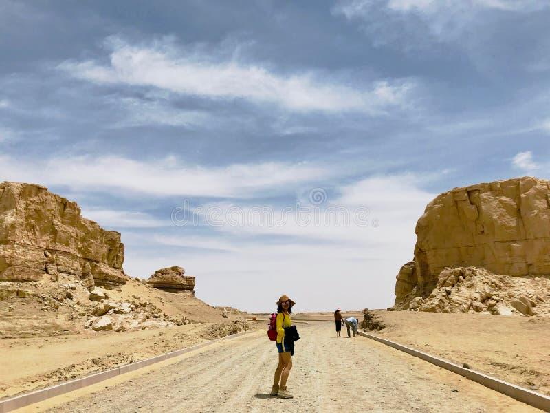 Une fille avec des sunglass marchant sur la route La vue du parc g?ologique national de Yardan, le Qinghai, Chine Yardang a ?t? c photos libres de droits
