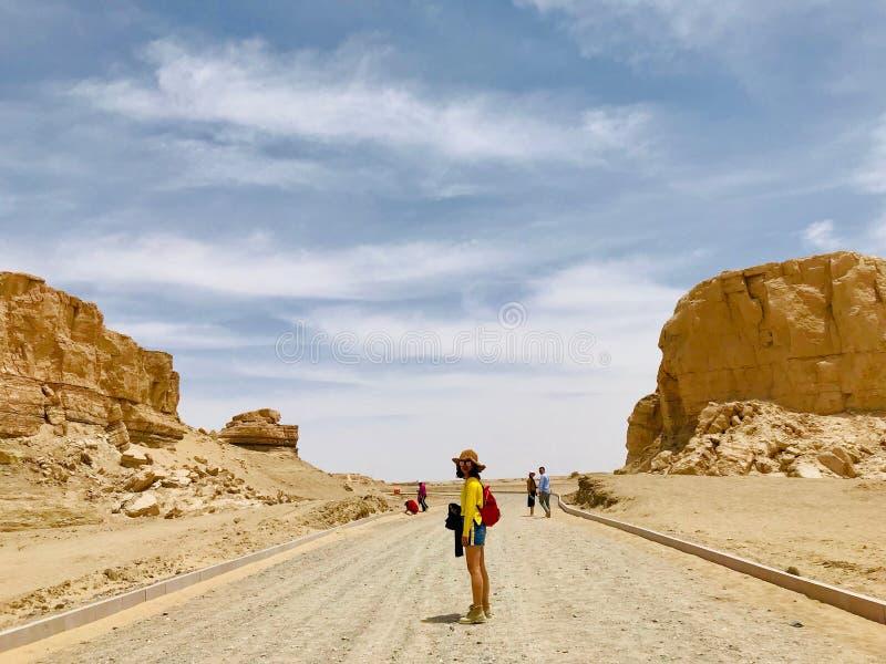 Une fille avec des sunglass marchant sur la route La vue du parc g?ologique national de Yardan, le Qinghai, Chine Yardang a ?t? c photographie stock libre de droits