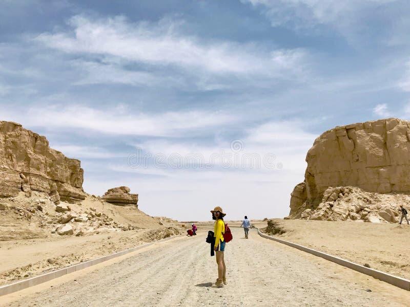 Une fille avec des sunglass marchant sur la route La vue du parc g?ologique national de Yardan, le Qinghai, Chine Yardang a ?t? c photo stock