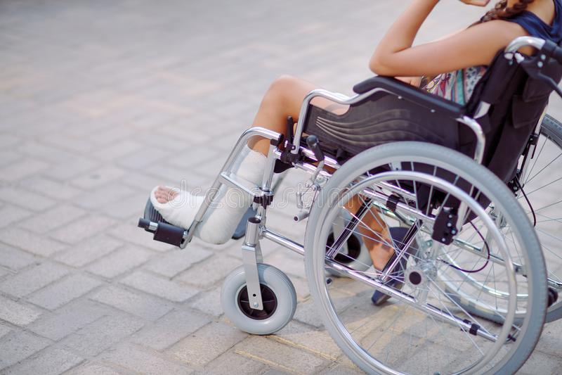 Une fille avec une jambe cassée s'assied dans un fauteuil roulant images stock