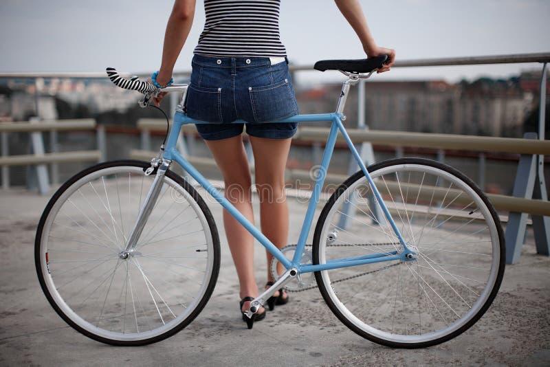 Une fille avec le vélo bleu image stock