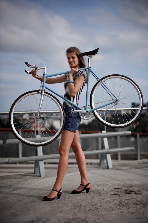 Une fille avec le vélo ciel-bleu photographie stock libre de droits