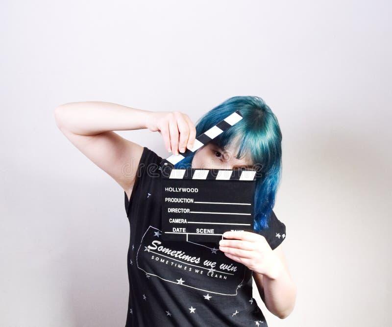 Une fille avec les cheveux bleus, tenant un clapet image stock