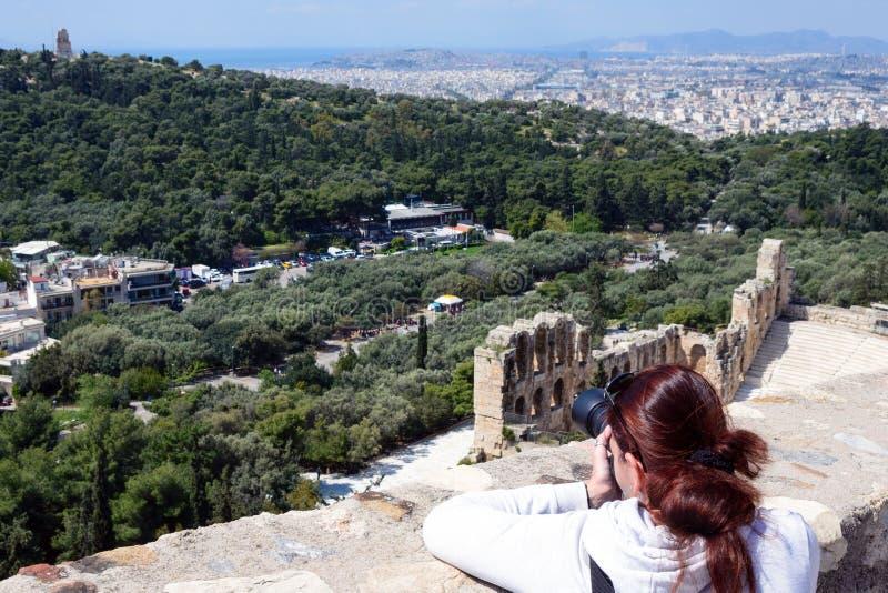 Une fille avec les cheveux bruns prend des photos de l'Odeon Ruines du grec ancien, ruines parmi l'herbe verte luxuriante Acropol photos libres de droits