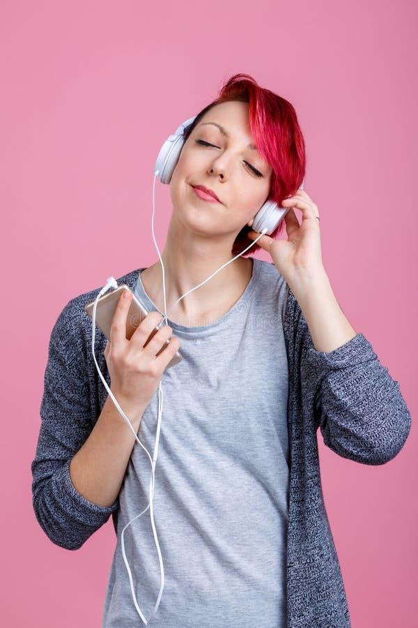 Une fille avec les cheveux rouges apprécie la musique dans des écouteurs photo stock