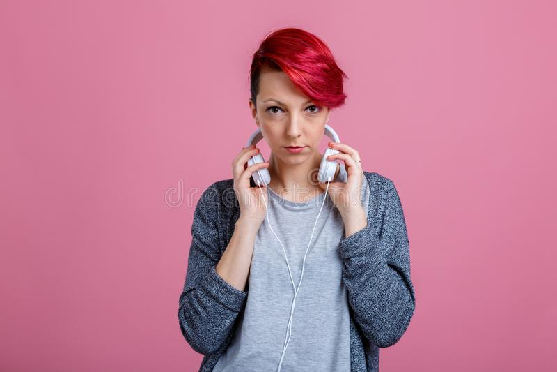 Une fille avec les cheveux rouges, tenant ses mains au-dessus des écouteurs blancs qui sont sur son cou photographie stock libre de droits