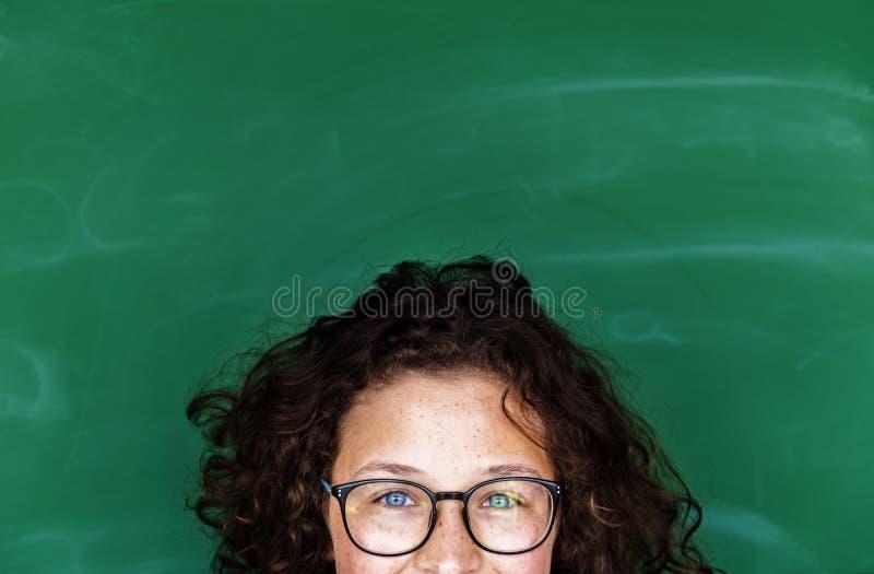 Une fille avec les lunettes et le tableau noir photo libre de droits