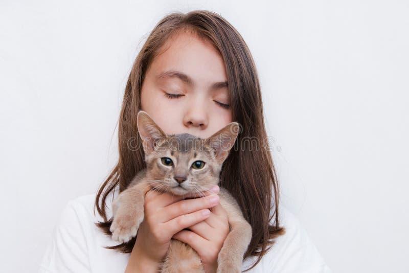 Une fille avec les yeux fermés avec son chaton d'animal familier sur ses mains posant pour l'appareil-photo photo libre de droits